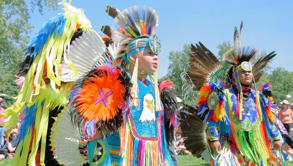 Aboriginal peoples are dancing wearing traditional costumes